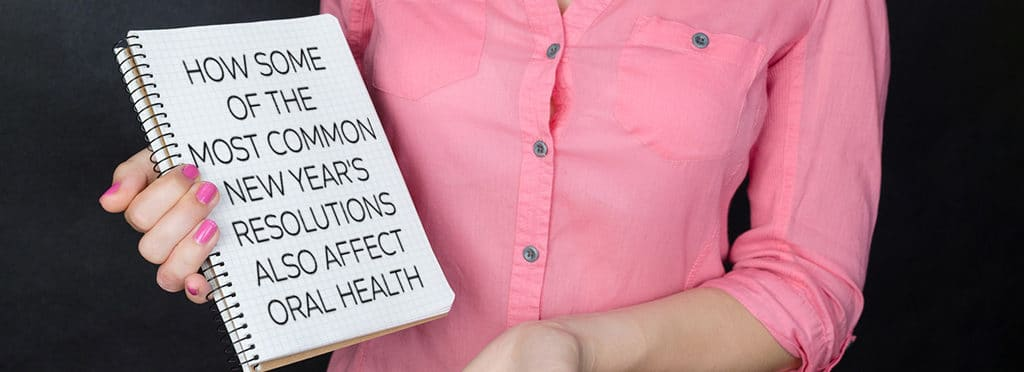 woman in a pink shirt holding a notebook